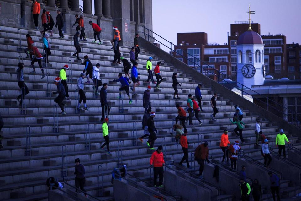 Members of the November Project run the steps at Harvard Stadium on Wednesday mornings. On Christmas Day, they wore Santa hats.
